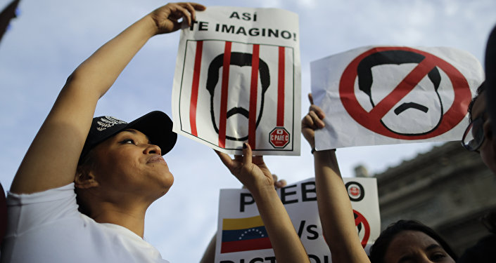 Venezuelan anti-government protesters hold signs against Venezuelan President Nicolas Maduro during a demonstration in Buenos Aires, Argentina, Wednesday, Jan. 23, 2019