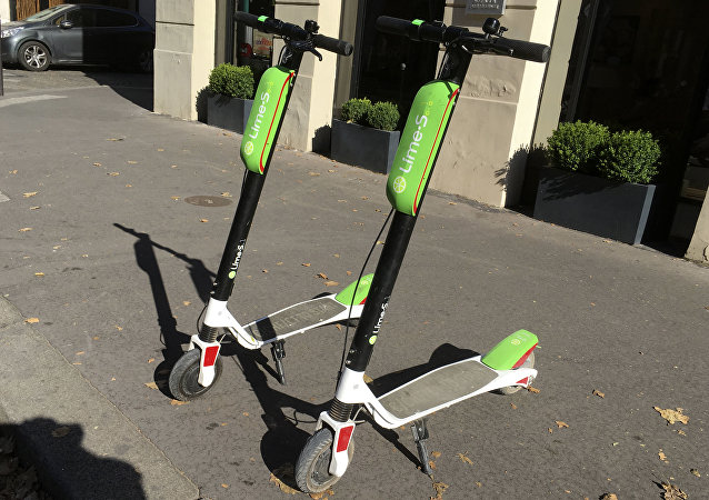 This July 3, 2018, photo shows scooters by Lime in Paris. Uber is getting into the scooter-rental business. The ride-hailing company said Monday, July 9, that it is investing in Lime, a startup based in San Mateo, California.