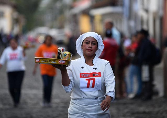 A waitress participates in the XVI Carrera de Charolas (Waiters Race) in Antigua Guatemala,45 km southwest of Guatemala City, on November 14, 2018.