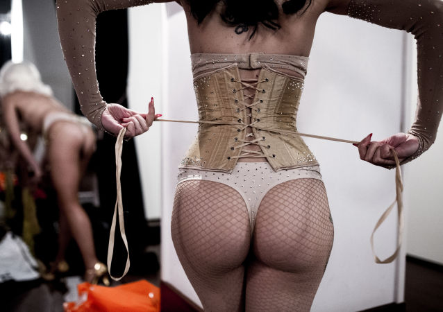 Miss Rudy Ruby ties her corset prior to performing in a burlesque show in Madrid