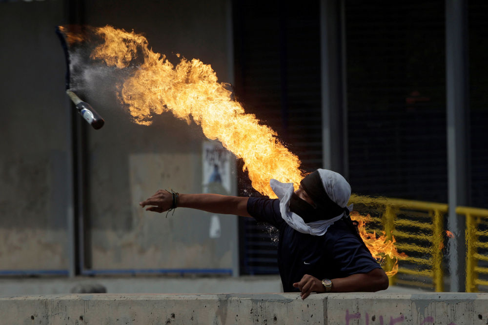 A demonstrator throws a petrol bomb at police in Honduras