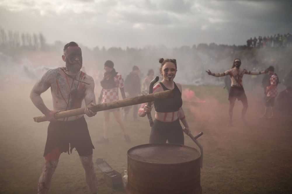 Performers beat their drums and release flares in an attempt to motivate competitors prior to the start of the Tough Guy endurance event near Wolverhampton