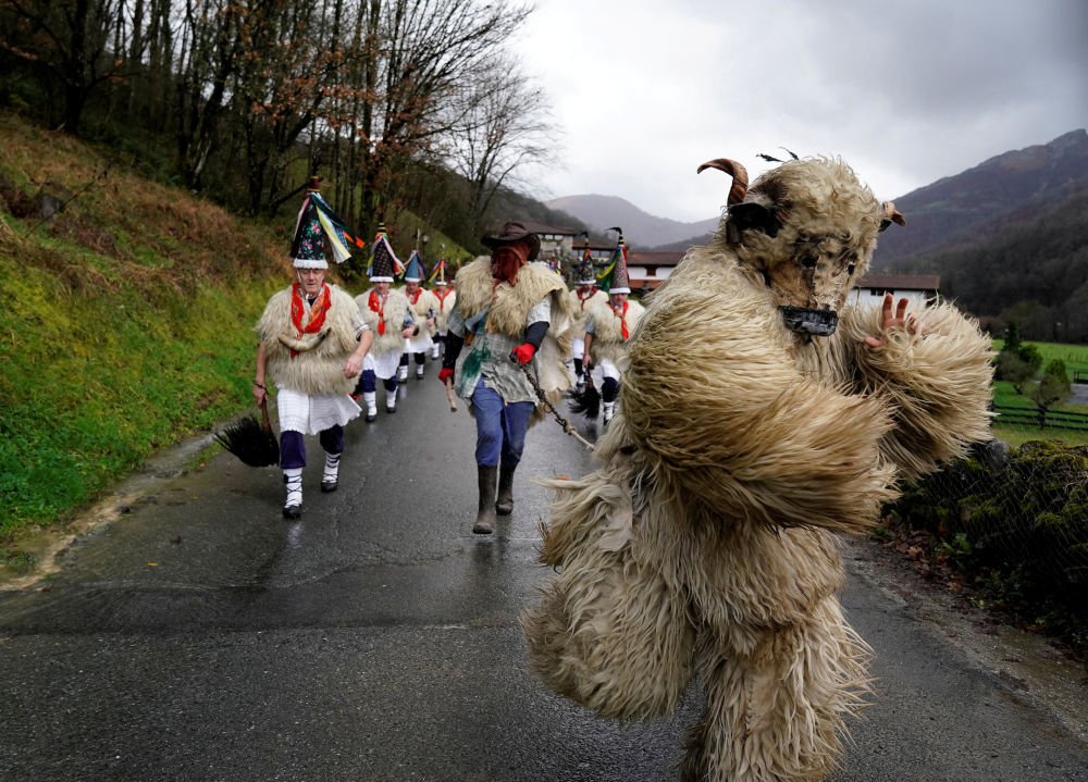 A man dressed as a bear accompanies bell-wearing dancers, known as Joaldunak, performing a ritual dance in Ituren, northern Spain