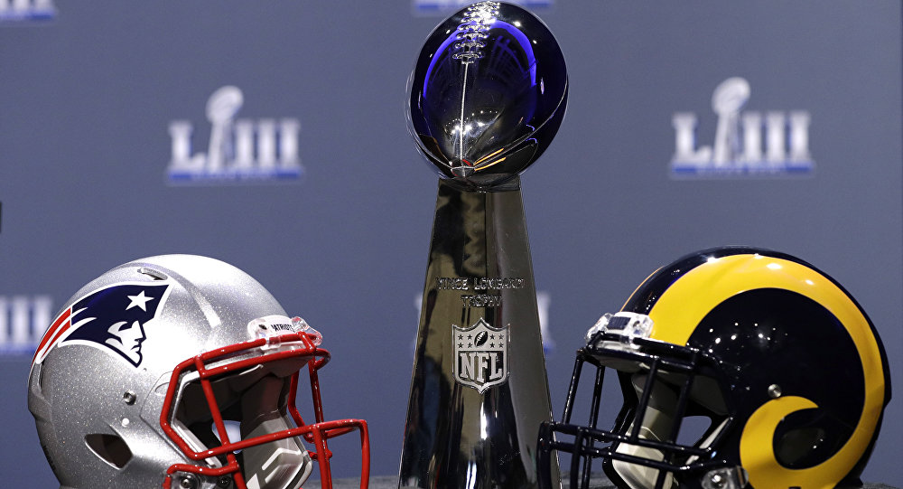 The helmets of the New England Patriots and the Los Angeles Rams next to the Superbowl trophy
