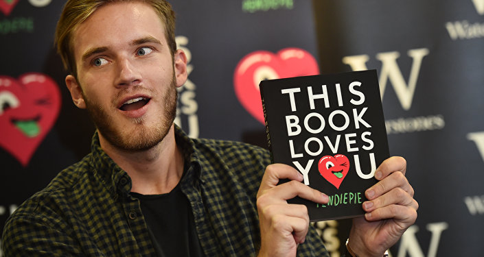 Felix Kjellberg, aka PewDiePie poses with his new book, 'This book loves you' at an event in central London, on October 18, 2015