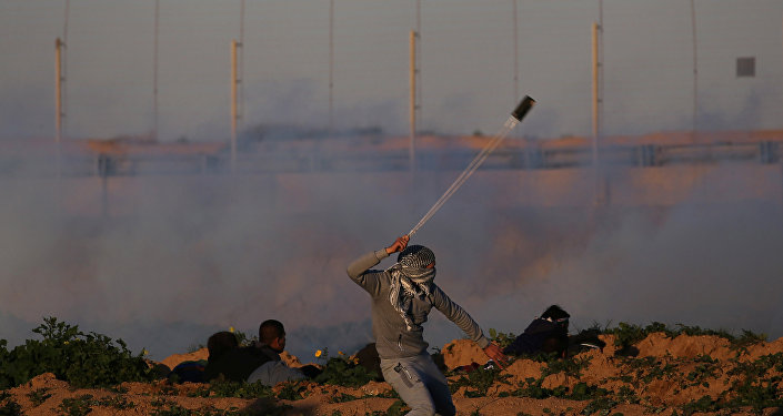 A Palestinian demonstrator hurls stones at Israeli troops during a protest at the Israel-Gaza border fence, in the southern Gaza Strip January 18, 2019