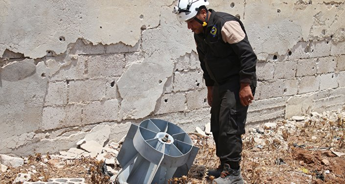 A member of the Syrian civil defence volunteers, also known as the White Helmets, stands next to the tail fin of a bomb as local bomb-disposal experts search for unexploded ordnance in a rebel-held area of Daraa on July 20, 2017