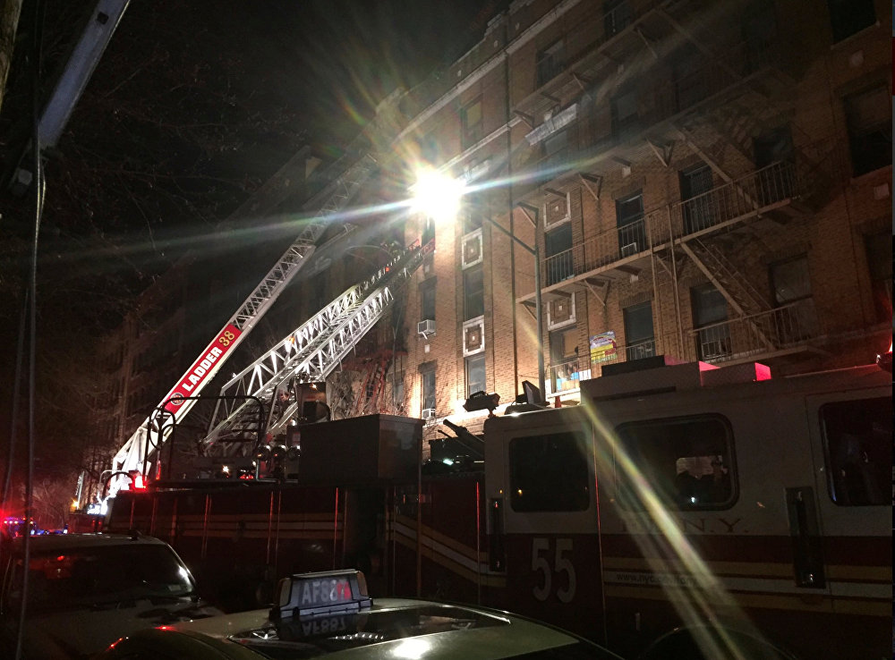 New York Fire Department ladder trucks deploy at a building fire in the Bronx borough of New York City