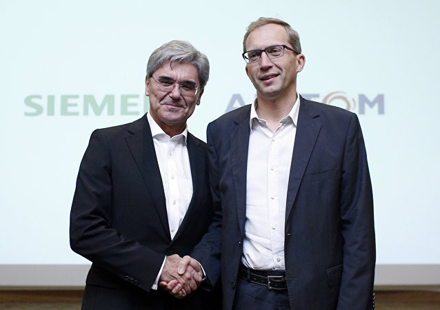 Alstom CEO Henri Poupart-Lafarge, right, shakes hands with Siemens CEO Joe Kaeser in Paris (File)