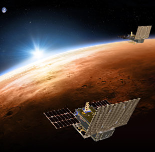 This illustration made available by NASA on March 29, 2018 shows the twin Mars Cube One (MarCO) spacecraft flying over Mars with Earth and the sun in the distance