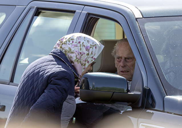 Britain's Prince Philip sits in the driving seat of a car, talking to his wife, Queen Elizabeth II