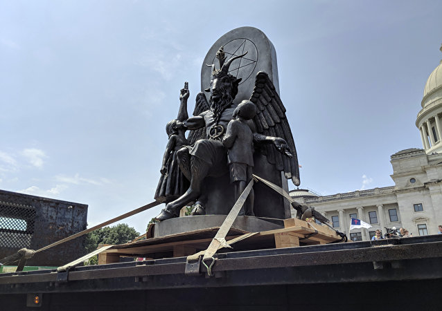 The Satanic Temple unveils its statue of Baphomet, a winged-goat creature, at a rally for the first amendment in Little Rock, Ark., Thursday, Aug. 16, 2018