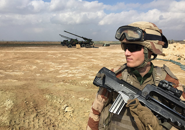 A French soldier engaged in the Operation Chammal, the French military operation within Operation Inherent Resolve, the international coalition against the Islamic State (IS) group, stands guard by three wheeled 155 mm gun-howitzer CAESAR systems (trucks equipped with an artillery system) on February 9, 2019, near Al-Qaim, a few kilometres away from the last scrap of territory held by IS in eastern Syria