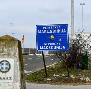 Workers clean up near the sign at the border between Macedonia and Greece, near Gevgelija, on February 11, 2019.