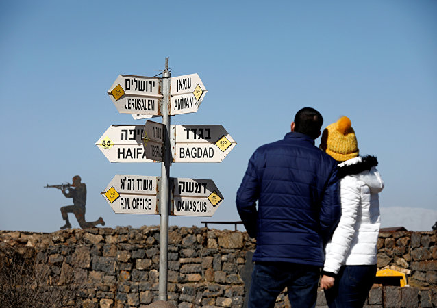 A couple look towards signs pointing out distances to different cities, on Mount Bental, an observation post in the Israeli-occupied Golan Heights that overlooks the Syrian side of the Quneitra crossing, Israel January 21, 2019