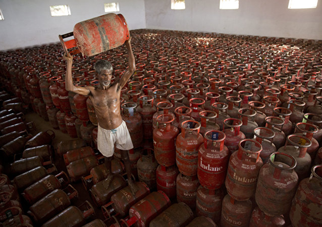 An Indian laborer sorts liquefied petroleum gas (LPG) cylinders used for cooking at a warehouse after downloading them from a truck in Allahabad, India (File)