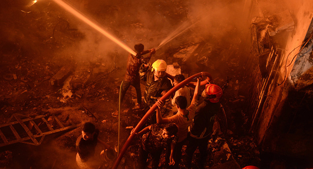 In this Wednesday, Feb. 20, 2019, photo, firefighters try to douse flames in Dhaka, Bangladesh.