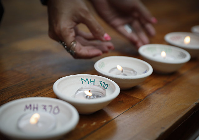 Relative of passengers on board the missing Malaysia Airlines Flight MH370 light up candle during the Day of Remembrance for MH370 event