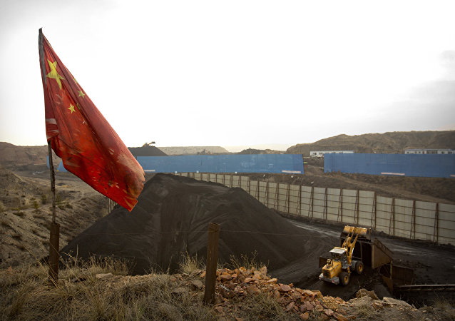 In this Wednesday, Nov. 4, 2015 photo, a Chinese flag moves in the breeze as a loader moves coal at a coal mine near Ordos in northern China's Inner Mongolia Autonomous Region.