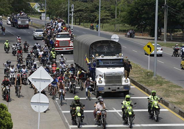Venezuelans ride atop and alongside semi-trailers accompanying US  humanitarian aid destined for Venezuela, in Cucuta, Colombia. File photo
