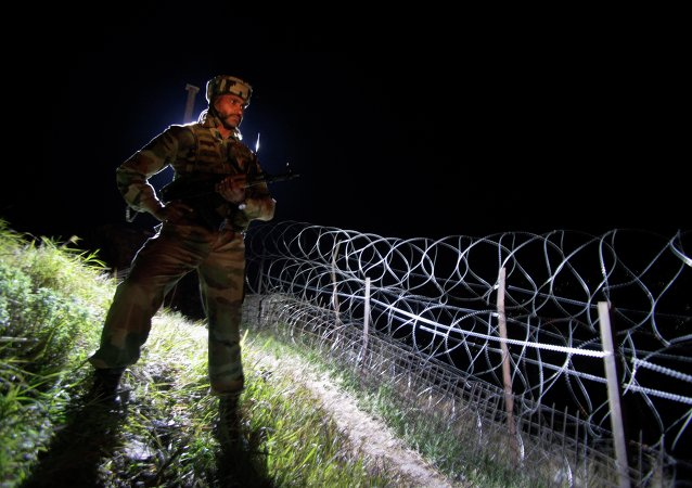 In this Dec. 22, 2013 photo, an Indian army soldier stands guard along barbed wire near the Line of Control (LOC), that divides Kashmir between India and Pakistan, at Krishna Ghati (KG Sector) in Poonch, 290 kilometers (180 miles) from Jammu, India
