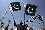 People carry national flags as they celebrate, after Pakistan shot down two Indian military aircrafts, in Lahore, Pakistan February 27, 2019