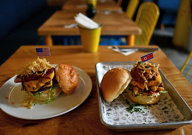 A Dirty Donald burger (L) and a Kim Jong Yum burger (R) is placed on a table at the Durty Bird restaurant in Hanoi on February 21, 2019