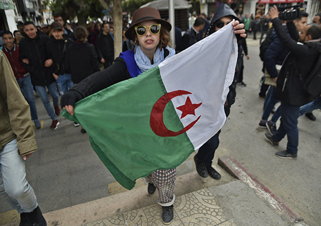 A woman holds an Algerian flag during demonstrations against President Bouteflika in Algiers on 26 February