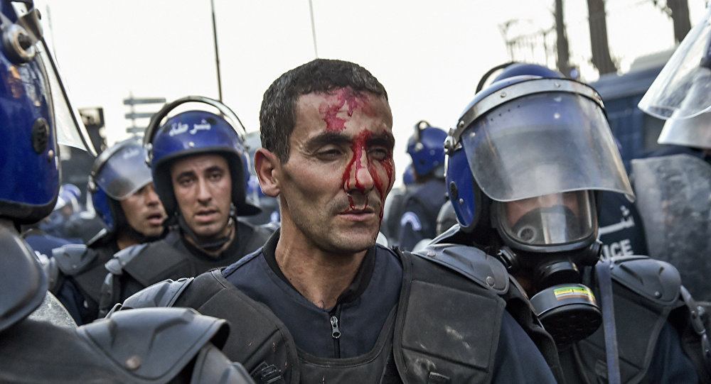 A member of the Algerian security forces is seen with a bloodied face as riot forces respond to protests in the capital Algiers on March 1, 2019, against ailing President Abdelaziz Bouteflika's bid for a fifth term in power.
