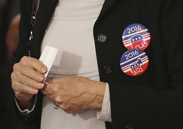 A woman wears badges for Democratic Party and Republican Party on her jacket during a live broadcasting of the 2016 U.S. Presidential Election results