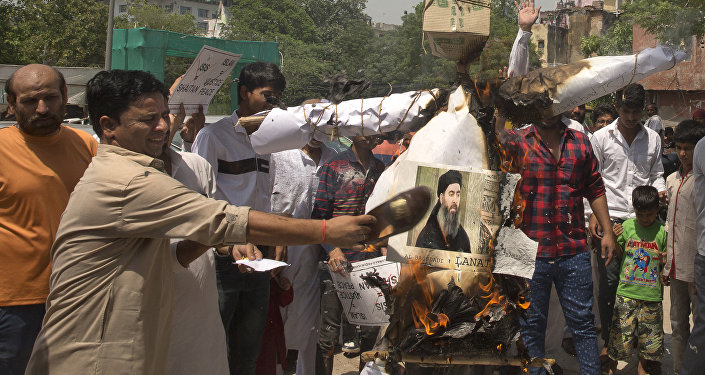 Shiite Muslims shout slogans and burn an effigy of the leader of the Islamic State group, Abu Bakr al-Baghdadi during a protest in New Delhi, India, Friday, June 9, 2017