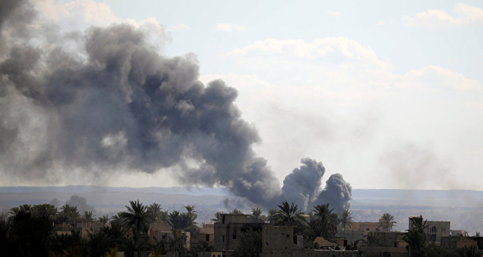 Black plumes of smoke rise in Baghouz, Deir ez-Zor province