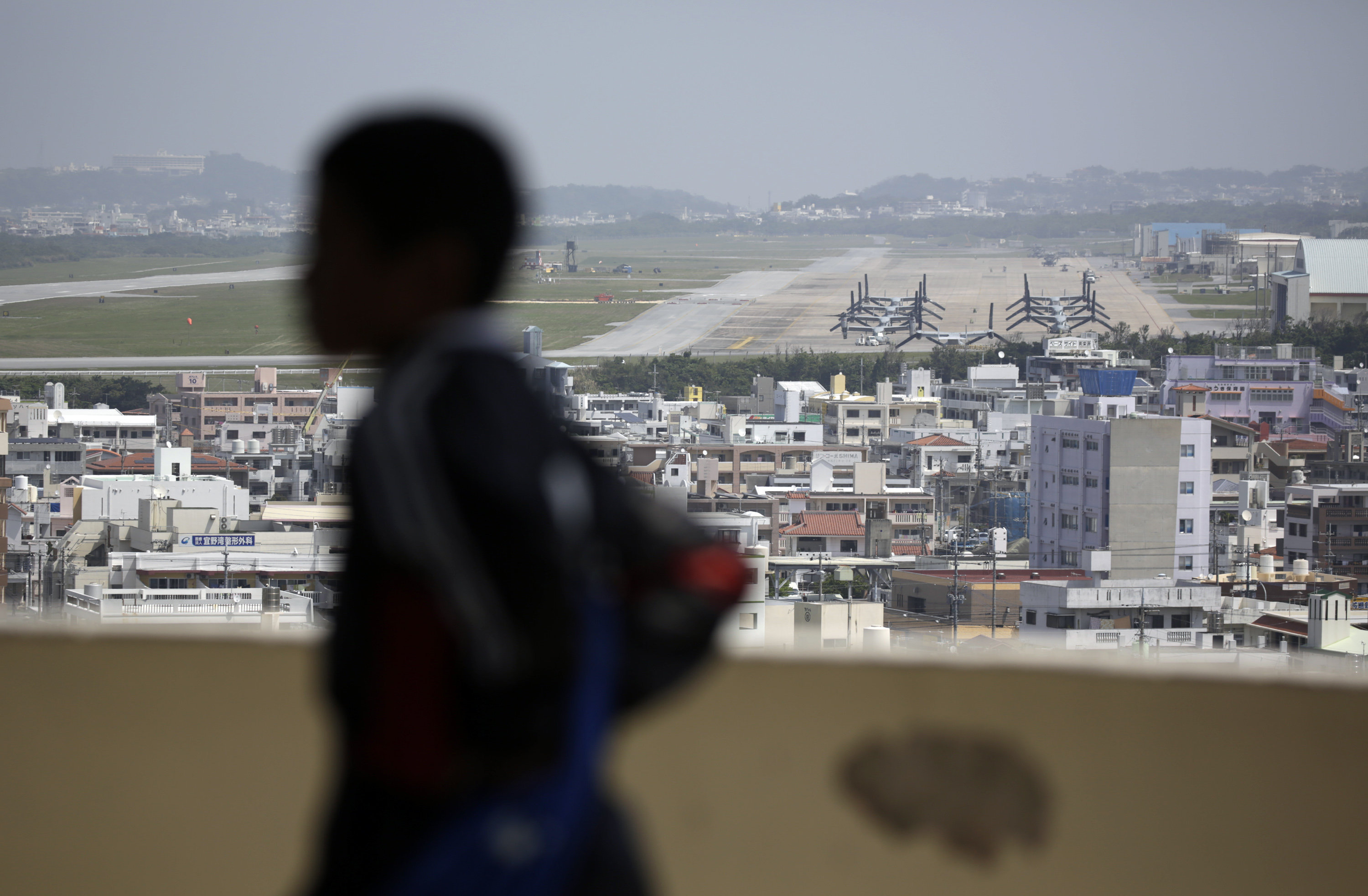 A child looks at the U.S. Marine Corps Futenma Air Station and the surrounding area from an observation deck at a park in Ginowan, Okinawa Prefecture on southern Japan.