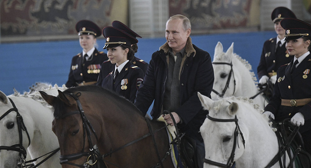 Putin rides a horse during a visit to a mounted police unit to congratulate female officers with International Women's Day.