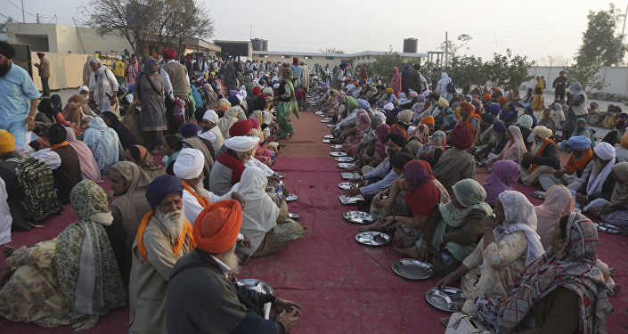 Sikh pilgrim wait for food at the shrine of their spiritual leader Guru Nanak Dev in Kartarpur, Pakistan, Wednesday, Nov. 28, 2018.