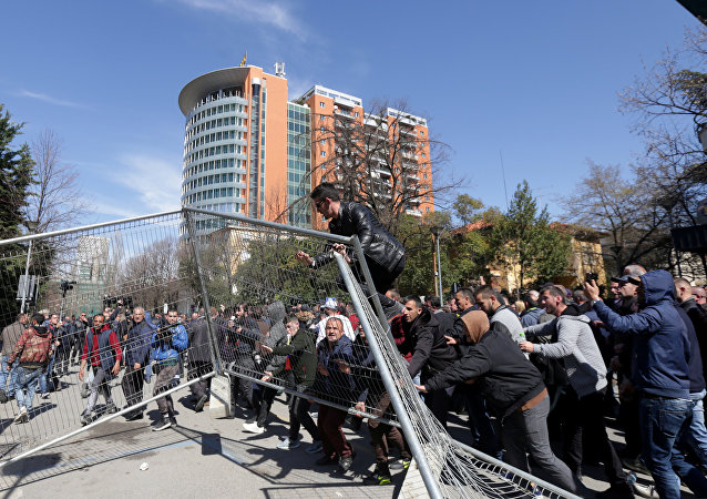 Supporters of the opposition party try to break through a police guarded fence near the office of Prime Minister Edi Rama during an anti-government protest in Tirana, Albania, March 16, 2019.