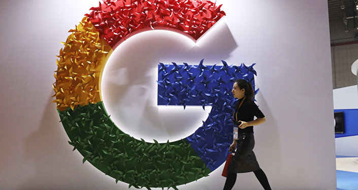 In this Monday, Nov. 5, 2018, photo, a woman carries a fire extinguisher past the logo for Google at the China International Import Expo in Shanghai