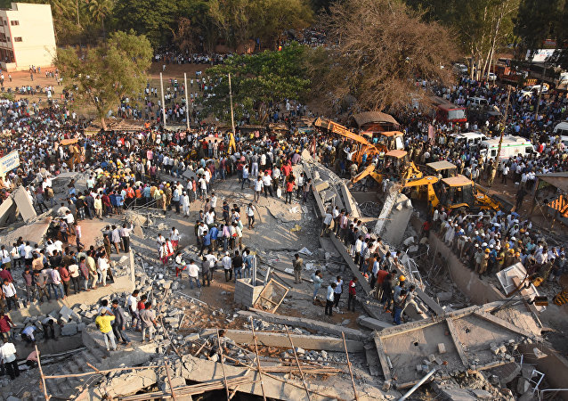 Onlookers gather near the rubble while rescue team search for survivors after an under-construction multi-storey building collapsed in Dharwad district of Karnataka