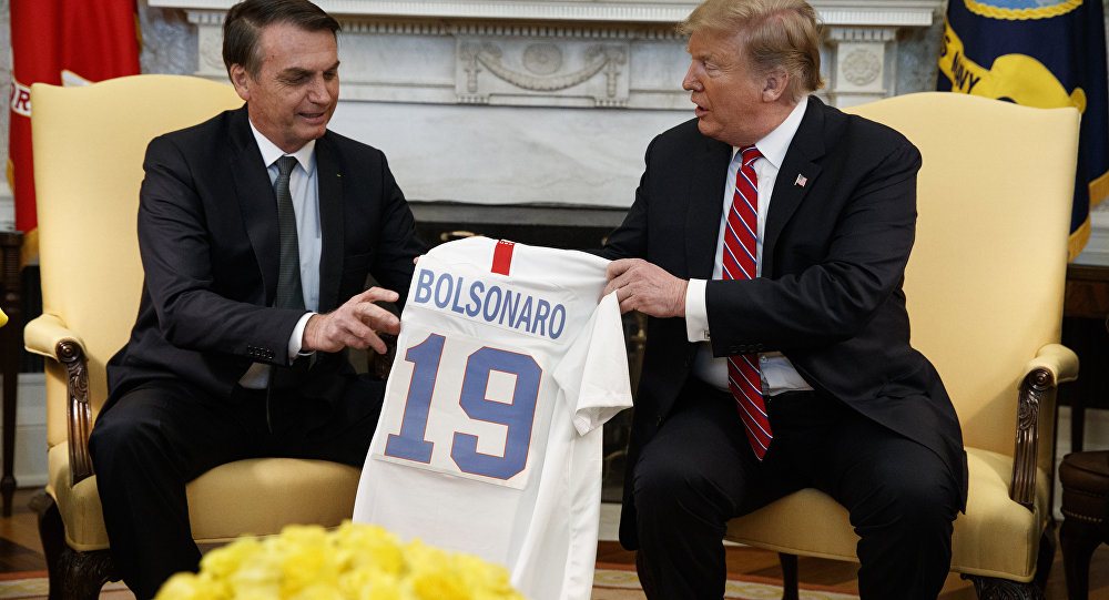 President Donald Trump presents Brazilian President Jair Bolsonaro with a U.S. national team soccer jersey during a meeting in the Oval Office of the White House, Tuesday, March 19, 2019, in Washington. (AP Photo/Evan Vucci)