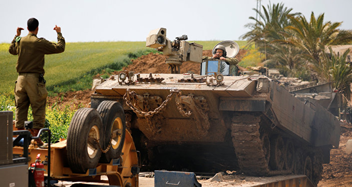 An Israeli soldier directs an armoured personnel carrier near the border between Israel and Gaza on its Israeli side