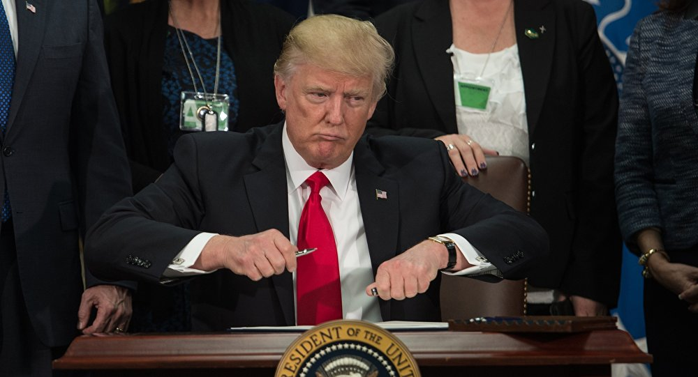 US President Donald Trump takes the cap off a pen to sign an executive order to start the Mexico border wall project at the Department of Homeland Security facility in Washington, DC, on January 25, 2017.
