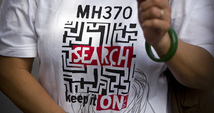 A relative of a Chinese passenger who was aboard missing Malaysia Airlines Flight 370 wears a shirt reading MH 370 Search - Keep it On as she speaks to the media near the Malaysian Embassy in Beijing, China, Thursday, Aug. 16, 2018