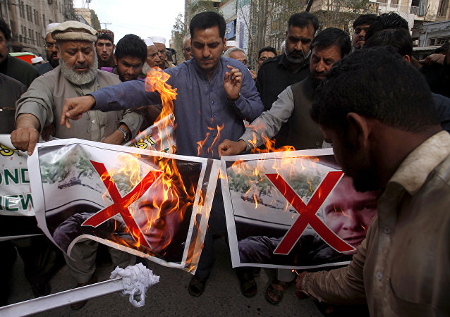 Pakistani traders burn pictures of Brenton Harrison Tarrant, one of the suspects in Christchurch mosques shooting during a demonstration to condemn mosque attack, in Peshawar, Pakistan, Saturday, March 16, 2019