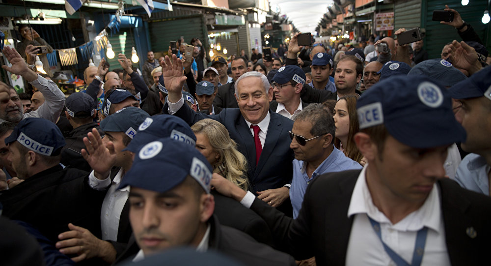 Israeli Prime Minister and head of the Likud party Benjamin Netanyahu, center, is escorted by security guards during a visit to the Ha'tikva market in Tel Aviv, Israel, Tuesday, April 2, 2019