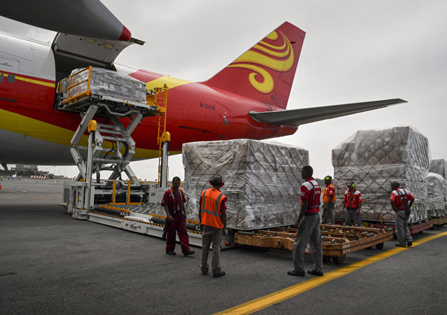 Workers unload medicines and disposable medical supplies from a Yangtze River Express Airlines Boeing 747 cargo plane after landing at Simon Bolivar International Airport on March 29, 2019 in Maiquetia, Vargas state, northern Venezuela. A Chinese plane loaded with 65 tons of medicines and medical supplies arrived in Venezuela