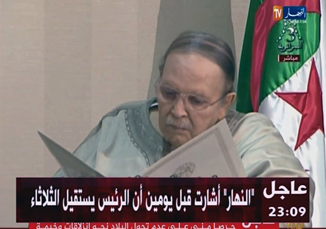 In this image from state TV broadcaster ENTV, Algerian President Abdelaziz Bouteflika, sitting in wheelchair, views the document as he presents his resignation to president of Constitutional Council Tayeb Belaiz, during a meeting Tuesday April 2, 2019.