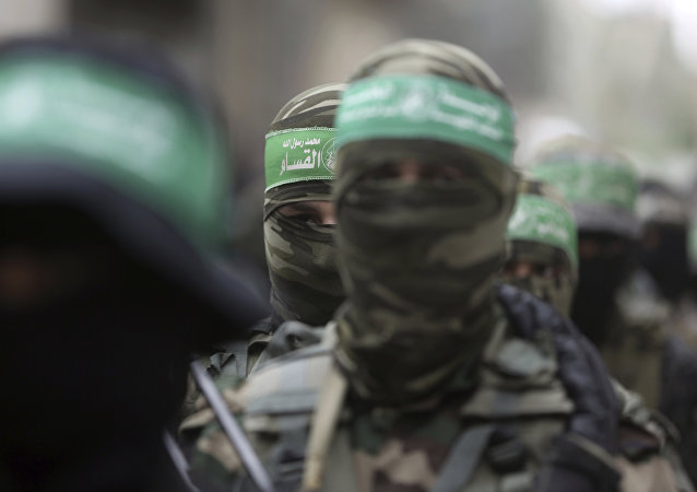 Masked Palestinian Hamas gunmen attend a funeral for six of their fighters who were killed in an explosion Saturday, in Deir el-Balah, central Gaza Strip