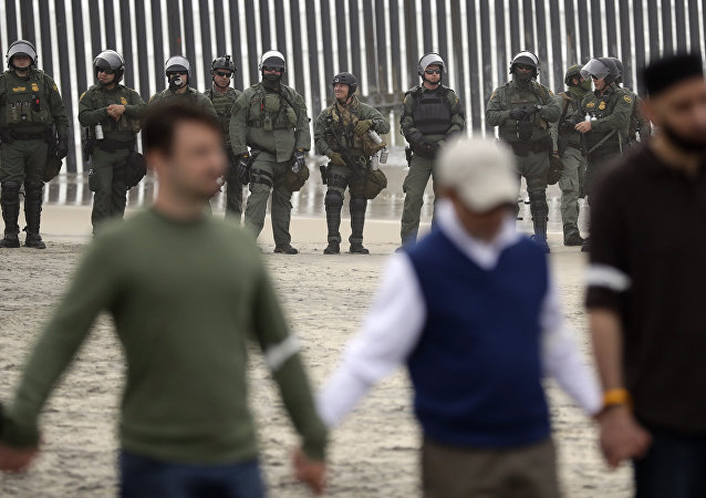 Border Patrol agents look on as a people hold hands and pray during a protest Monday, Dec. 10, 2018, in San Diego