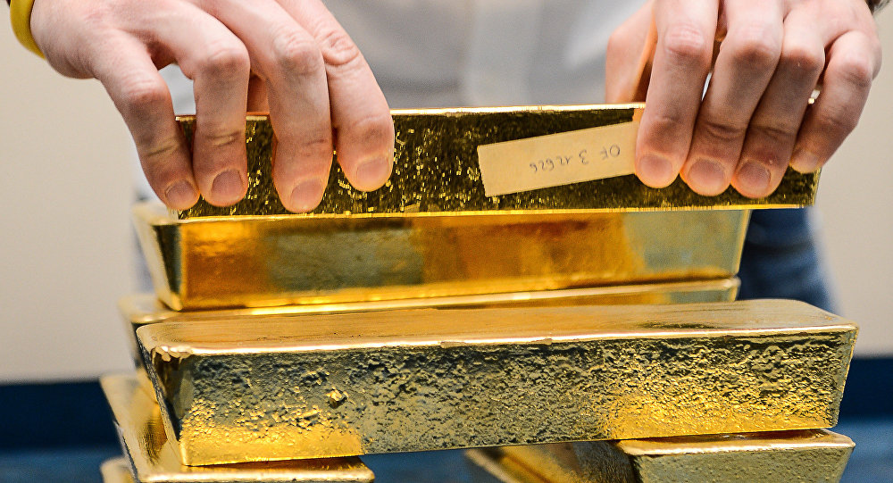 A metal analyst controls the weight of gold bars after the melting of gold, at Italpreziosi gold refinery company, in Arezzo, on 11 May, 2012