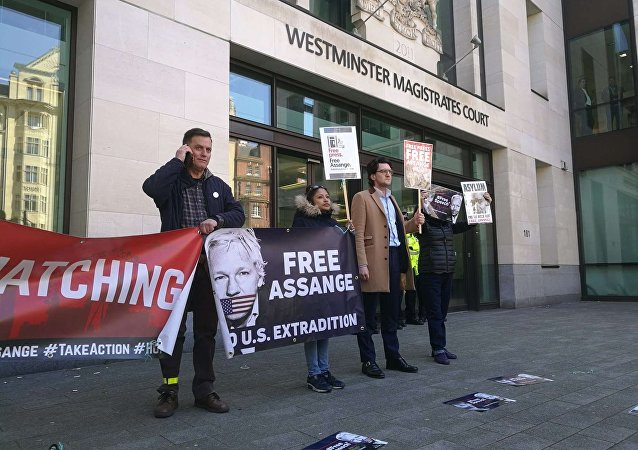 People are seen outside Westminster magistrates court in London, Thursday, April 11, 2019